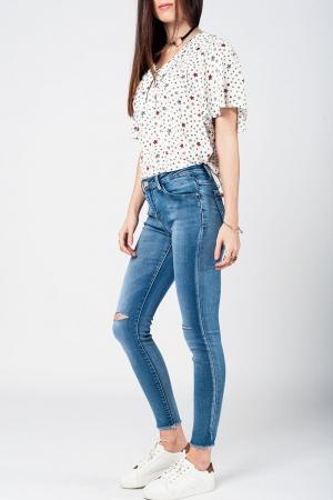 Jeans apertados com baixa joelho lavagem média desgastado e quebrado