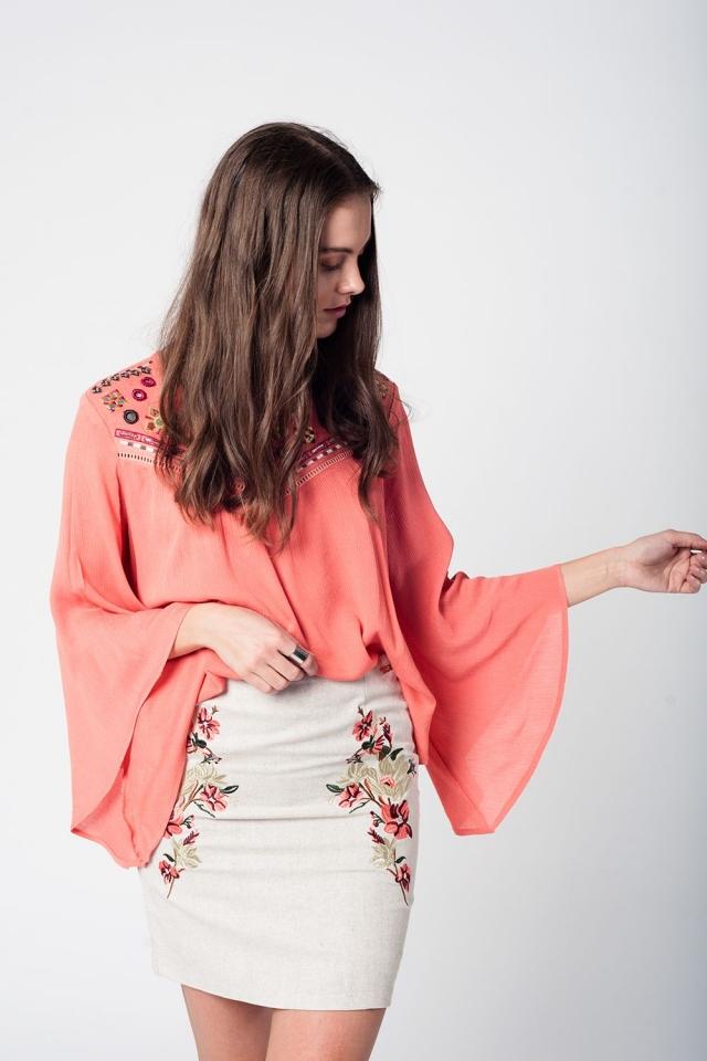 Blusa coral com detalhes bordados e mangas largas
