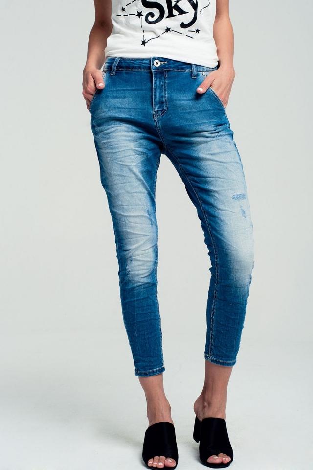 Calças de ganga elástica com abrasões e lavagem médio azul