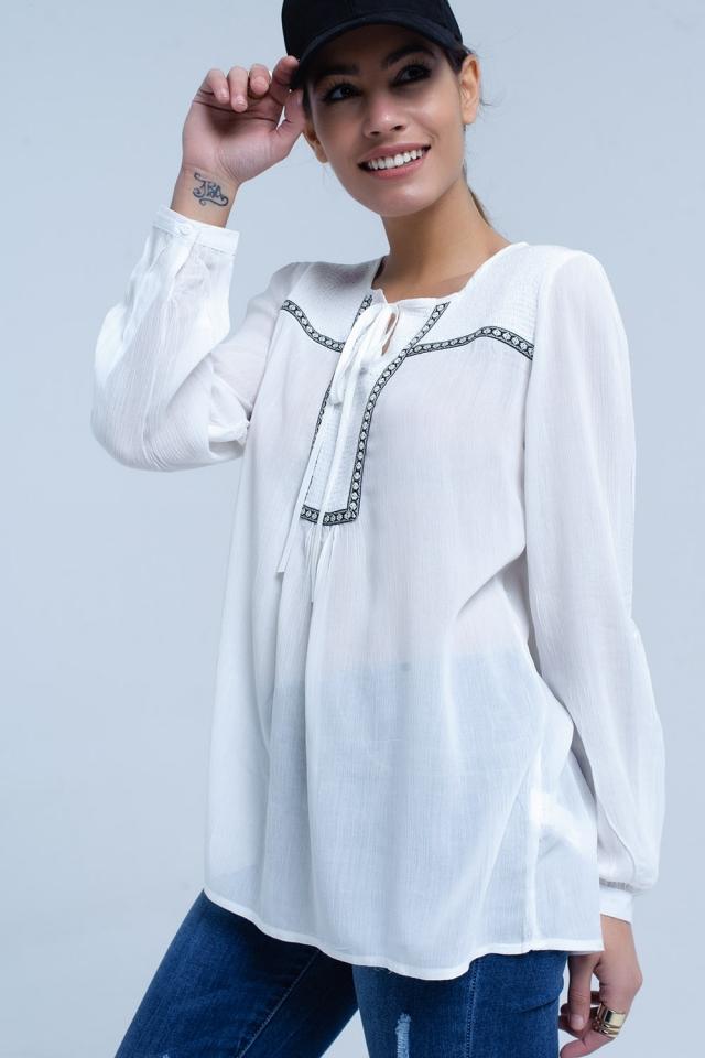 Blusa branca com guarnições bordadas