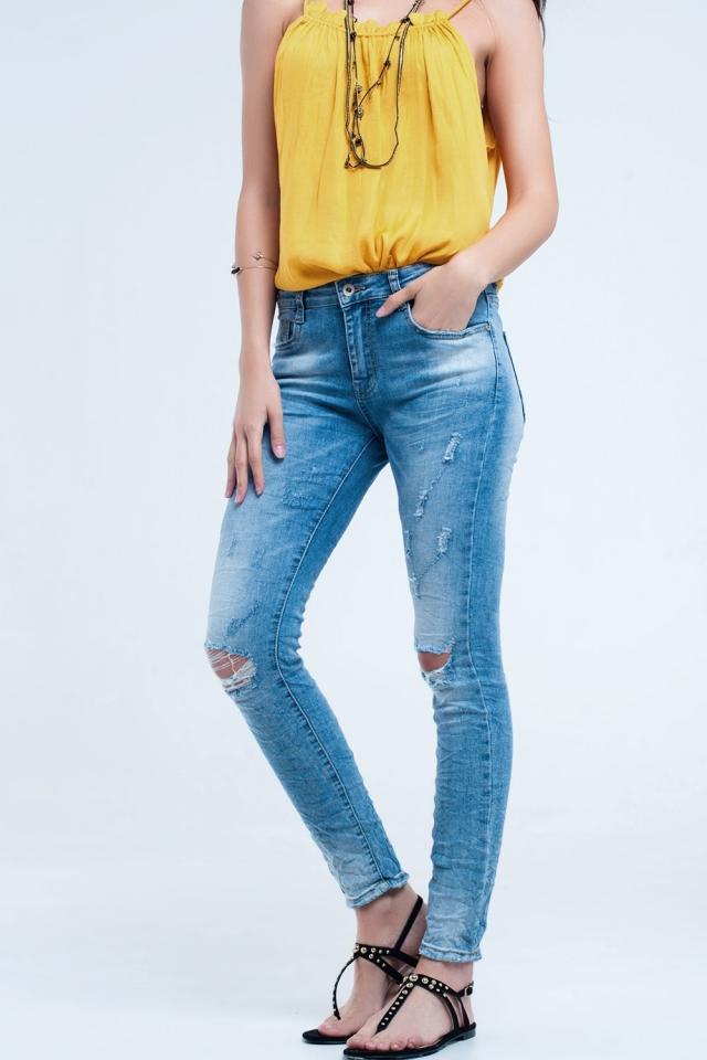 Calça jeans skinny no meio da lavagem com os joelhos rasgados