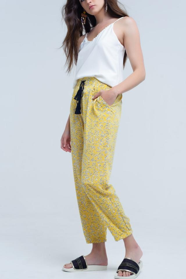 Calça amarela com folhas e bolsos impressos