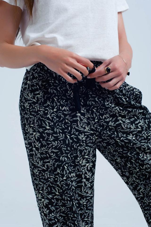 Calça preta com folhas e bolsos impressos