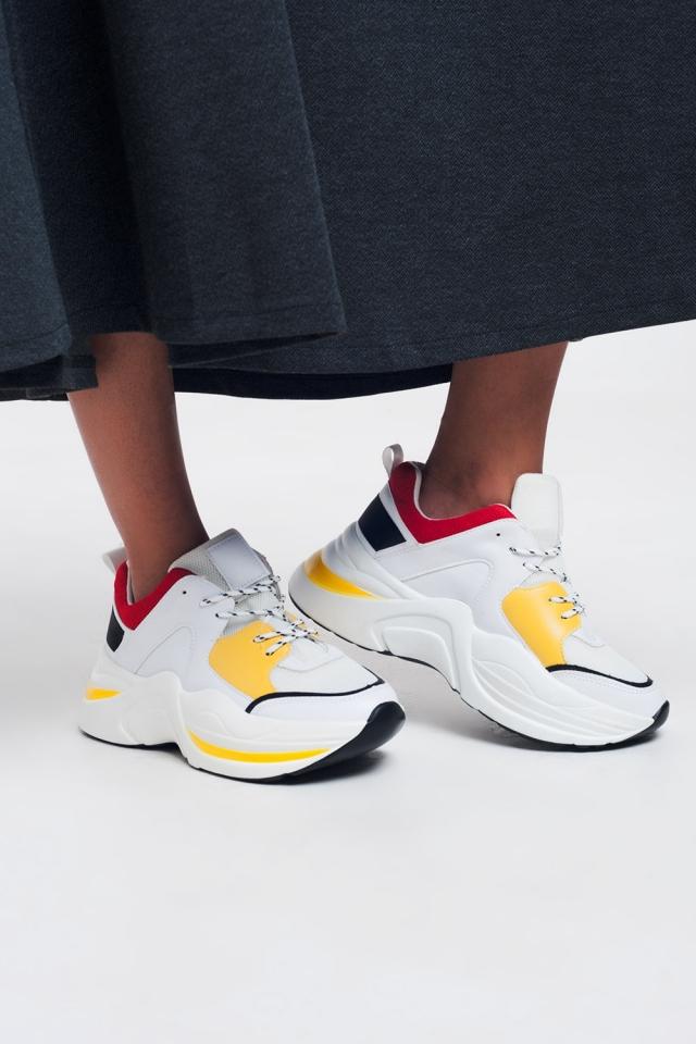 Tênis brancos com detalhes amarelos e vermelhos