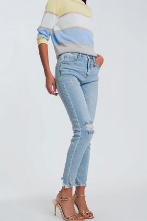Jeans skinny com fundo áspero e lágrimas nos joelhos azuis