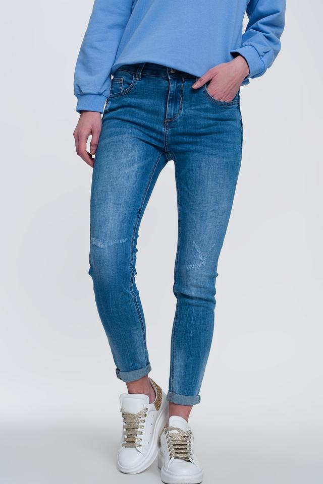 jeans skinny de denim claro com tornozelos dobrados e detalhes rasgados