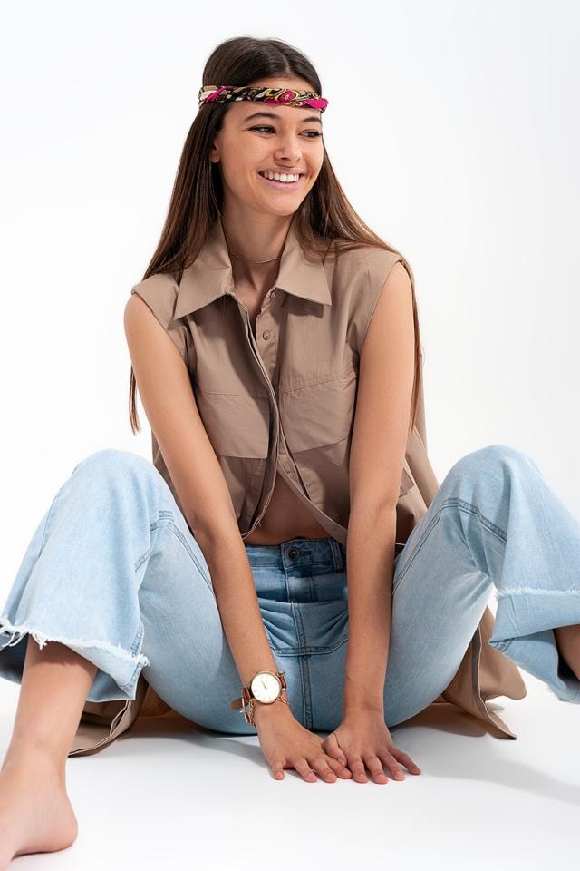 Camisa sem mangas bege com almofadas de ombro e compartimentos utilitários